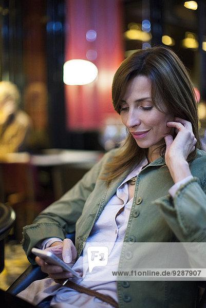 Frau in der Einkaufspause mit dem Smartphone