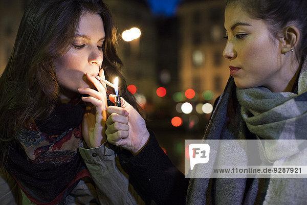 Frau beim Anzünden der Zigarette eines Freundes