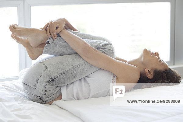 Frau liegt auf dem Bett  umarmt zufrieden die Knie