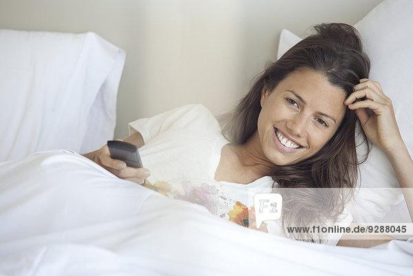 Frau beim Fernsehen im Bett