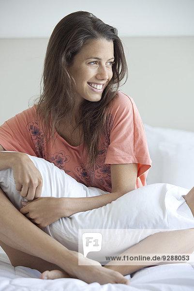 Frau auf dem Bett sitzend  Kissen haltend  nachdenklich wegschauend