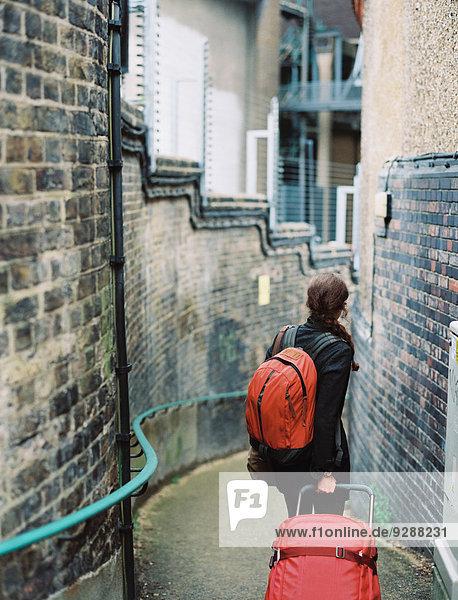 Eine Frau  die eine schmale Straße entlang mauert  einen Koffer zieht und einen orangefarbenen Rucksack in der Hand hält. Eine Frau, die eine schmale Straße entlang mauert, einen Koffer zieht und einen orangefarbenen Rucksack in der Hand hält.