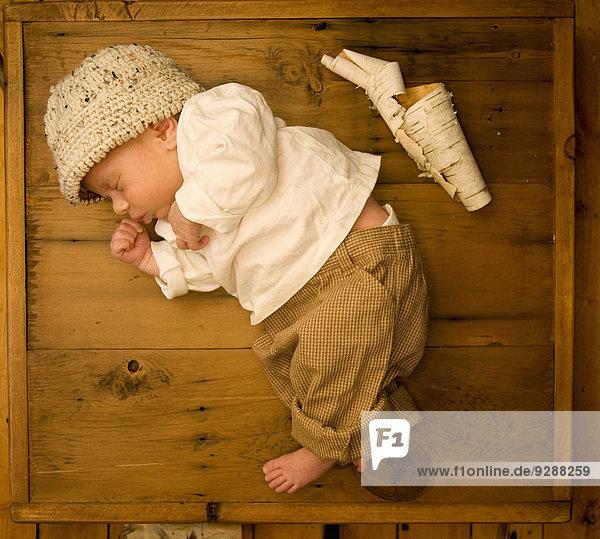 Ein neugeborenes Baby liegt schlafend auf der Seite in einer Holzkiste  neben ihm eine Schriftrolle aus weißer Baumrinde.