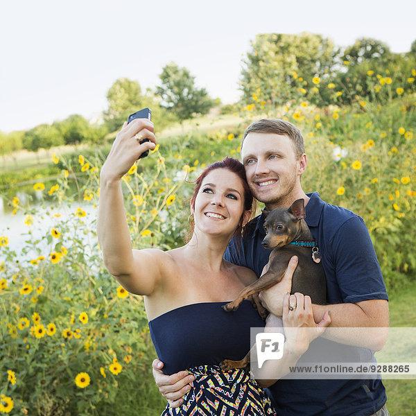 Ein Paar  das mit seinem kleinen Hund im Park spielt und sich ein Selfy nimmt.
