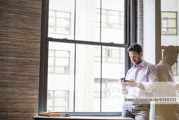 Büroalltag. Ein Mann in einem Büro  der sein Smartphone überprüft.
