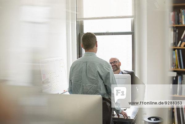 Büroalltag. Zwei Menschen  Geschäftsleute  die über ihren Schreibtisch miteinander reden.