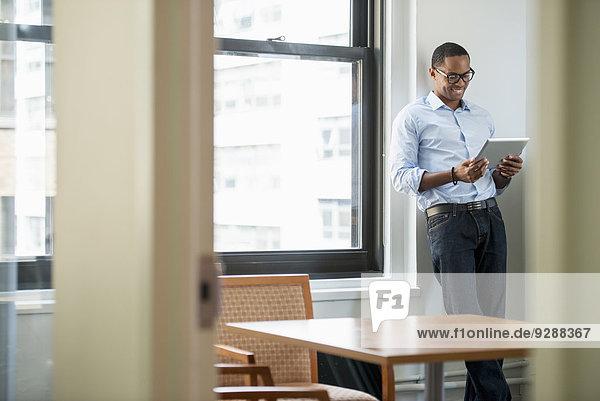 Ein Geschäftsmann  der ein digitales Tablett benutzt und an einem Fenster steht.