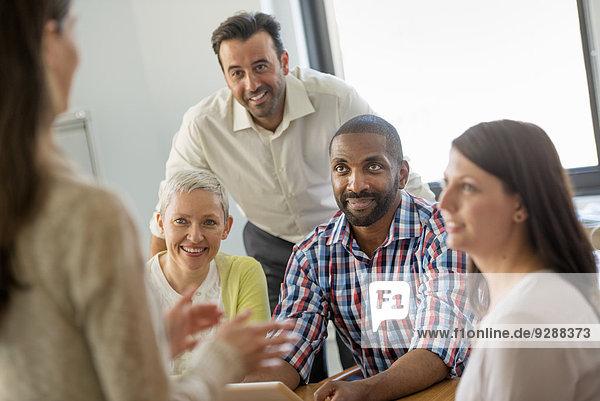 Fünf Personen in einem Büro  zwei Männer und drei Frauen im Gespräch.