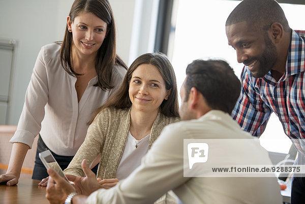 Vier Personen  Männer und Frauen  gruppierten sich um ein digitales Tablett und blickten auf den Bildschirm.