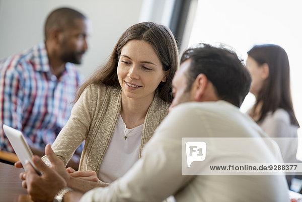 Vier Personen in einem Büro  zwei Männer und zwei Frauen  ein Paar  das auf den Bildschirm eines digitalen Tabletts schaut.