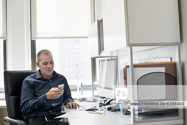 A man sitting at an office desk checking his smart phone.