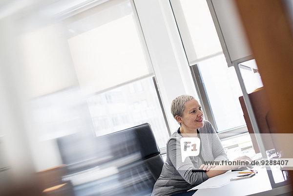 Eine Frau  die in einem Büro an einem Schreibtisch sitzt und eine Computermaus benutzt.