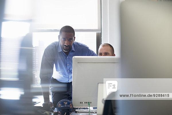 Zwei Männer  die in einem Büro arbeiten und beide auf einen Computermonitor schauen.