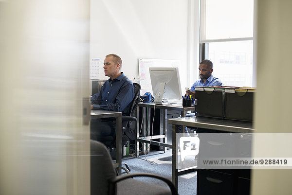 Two men working in an office  using computers.