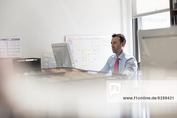 Ein Mann  der an einem Büroschreibtisch sitzt und einen Computer benutzt. Eine Wandkarte mit aufgeklebten Notizen.