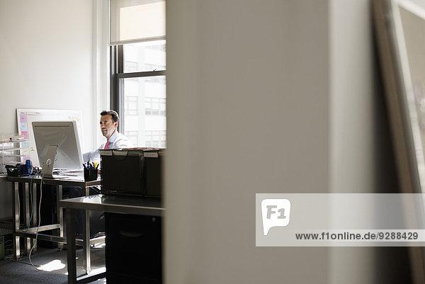 Ein Mann  der an einem Schreibtisch in einem Büro sitzt und einen Computer benutzt.