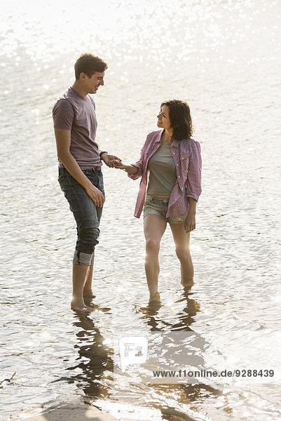 Ein Paar hält sich an den Händen und paddelt im flachen Wasser am See.