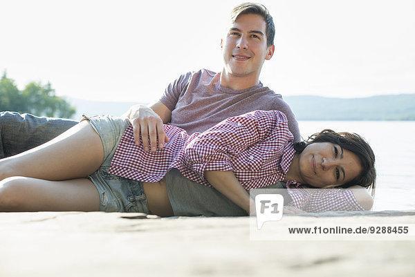 Ein Paar  das sich im Sommer auf einem Holzsteg an einem See entspannt.