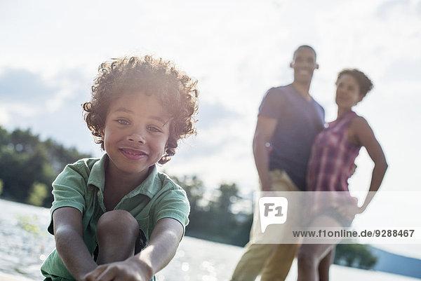 Eine Familie  Eltern und Sohn verbringen im Sommer gemeinsam Zeit an einem See.