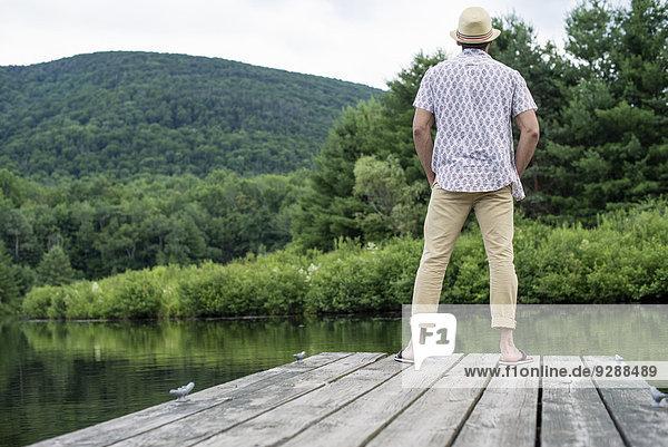 Ein Mann steht auf einem Holzsteg mit Blick auf einen ruhigen See.