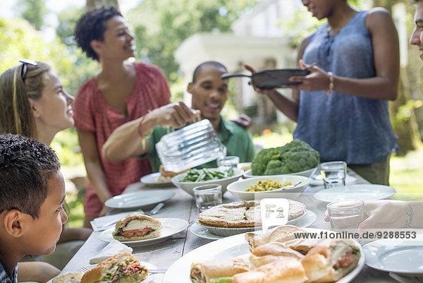 Ein Familientreffen  Männer  Frauen und Kinder um einen Tisch in einem Garten im Sommer.