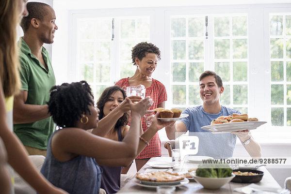Ein Familientreffen  bei dem Männer  Frauen und Kinder an einem Esstisch sitzen und gemeinsam essen.