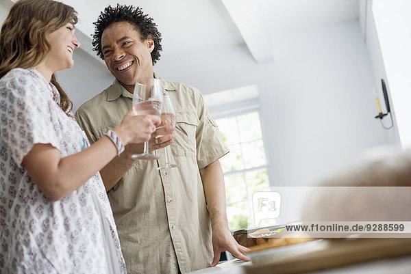 Menschen  die frische Lebensmittel an einen Familientisch tragen. Menschen, die frische Lebensmittel an einen Familientisch tragen.