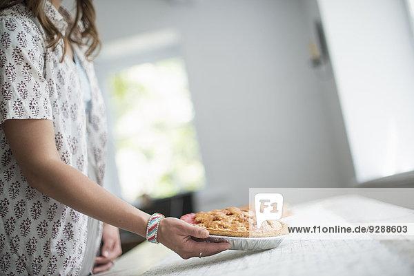 Eine Frau  die Essen zu einem Tisch trägt und sich für eine Familienmahlzeit vorbereitet. Eine Frau, die Essen zu einem Tisch trägt und sich für eine Familienmahlzeit vorbereitet.