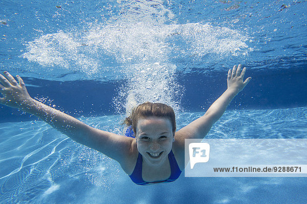 A young girl with long hair fanning out in the water  swimming underwater.