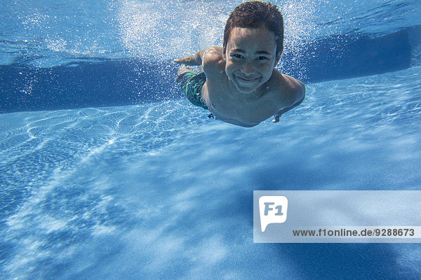 A boy swimming underwater smiling at the camera.