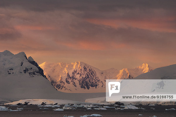 Sonnenuntergang über der gebirgigen Landschaft der Antarktis.