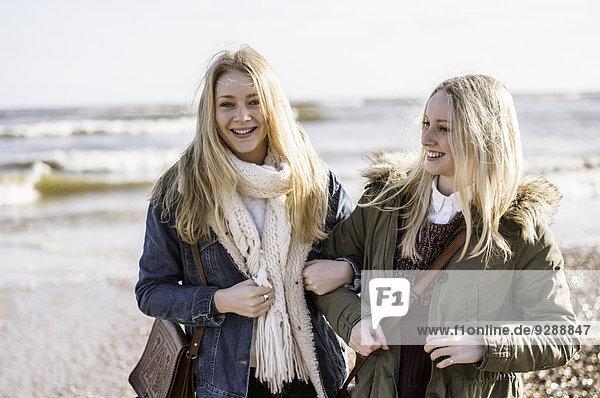Zwei junge Mädchen an einem Strand im Winter.