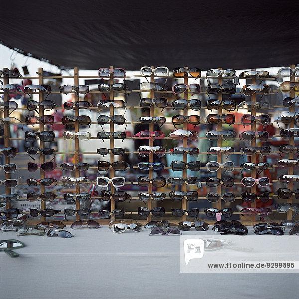 Eine große Auswahl an Sonnenbrillen zum Verkauf auf einem Flohmarkt