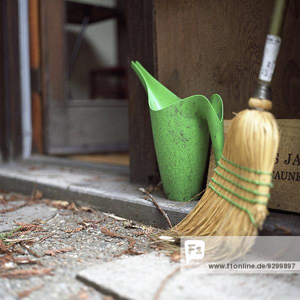 Besen und Gießkanne vor der Tür,  Nahaufnahme