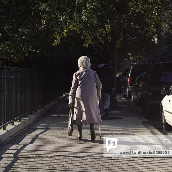Eine ältere Frau mit einem Stock auf einem Bürgersteig  Rückansicht
