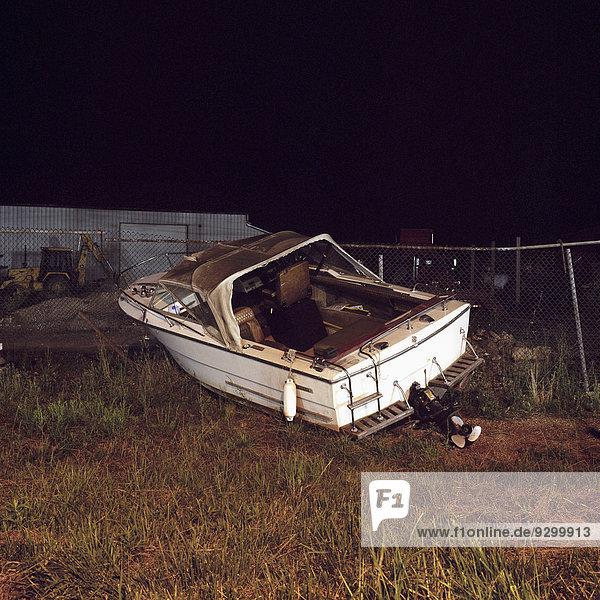 Ein verlassenes Motorboot auf einem leerstehenden Grundstück  Nachtzeit