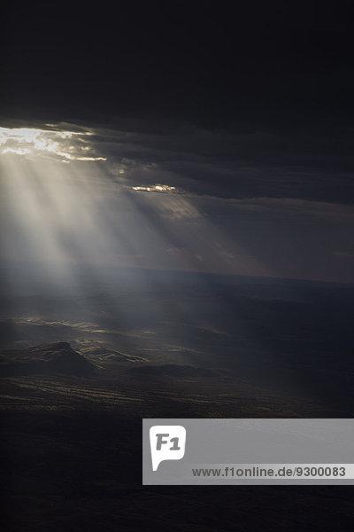 Durch Sturmwolken strömende Sonne auf trockener Landschaft