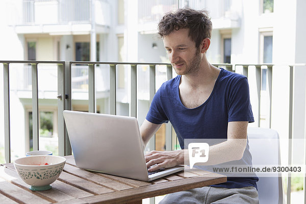 Young man using laptop at porch