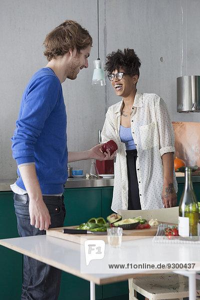 Glückliche Freunde bei der Zubereitung von Speisen in der Küche
