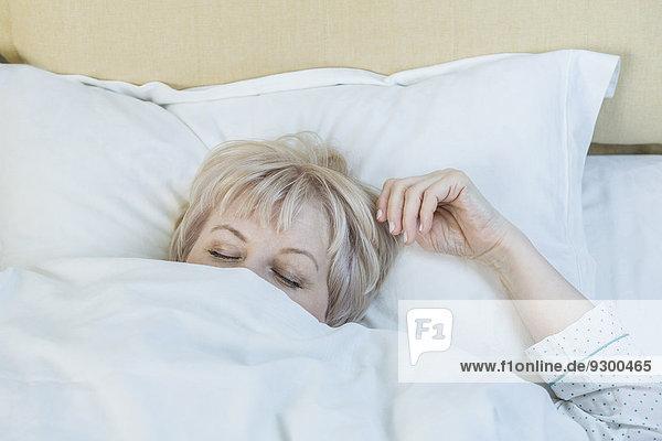 Reife Frau schläft im Bett