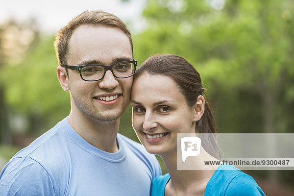 Porträt eines jungen Paares  das im Park lächelt.
