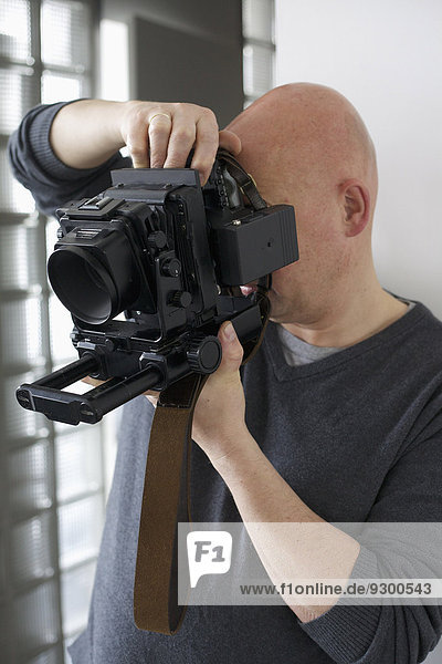 Mann fotografiert durch moderne Kamera zu Hause