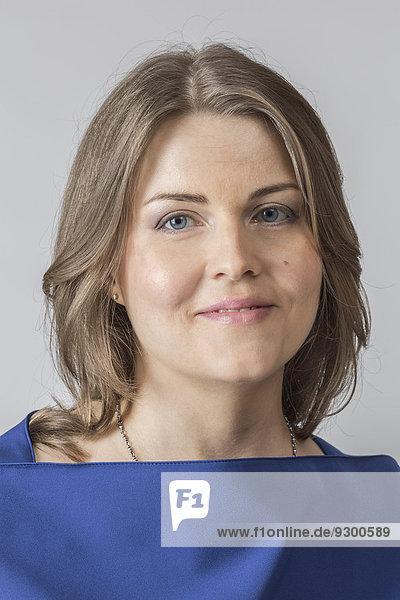 Porträt einer lächelnden Frau auf grauem Hintergrund
