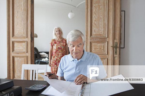 Senior Mann bei der Durchsicht von Finanzdokumenten mit Frau im Hintergrund zu Hause