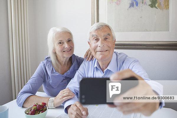 Glückliches Seniorenpaar beim Selbstporträt durch Smartphone am Tisch im Haus