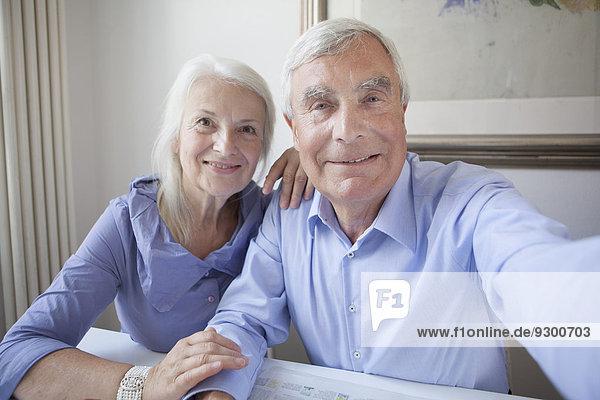 Porträt eines lächelnden Seniorenpaares  das zusammen am Tisch sitzt.