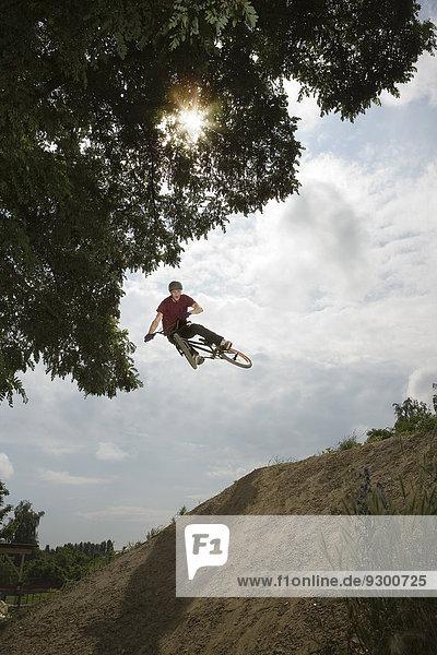 Ein BMX-Fahrer in der Luft an der Spitze einer Schlammpiste