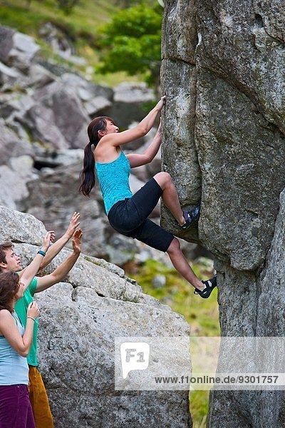 Reife Kletterin auf RAC-Blöcken  beobachtet von Freunden  Snowdonia  North Wales  UK