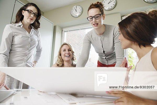 Vier Geschäftsfrauen auf der Suche nach der Blaupause im Büro