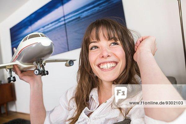 Frau spielt mit Spielzeugflugzeug